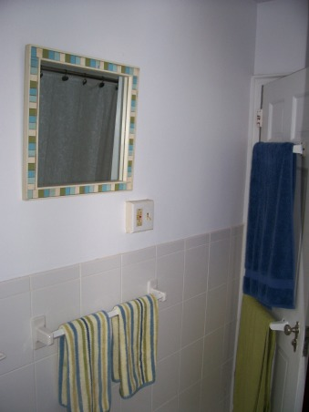 Small Seaside Bathroom, My only bathroom is tiny. Landlord doesn't want me painting it because he just renovated it before I moved in.  Tried to jazz it up with beach theme, but feel something is still lacking from making it pop. Really ugly and non-working fan is built into wall above toilet.  How can I mask it?, Right side of picture is edge of doorway. Wall w/ mirror is opposite tub.Sink is to left of mirror (not shown). , Bathrooms Design