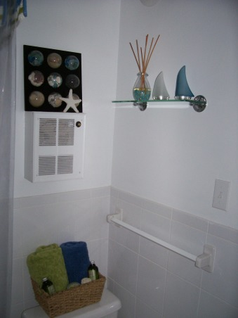 Small Seaside Bathroom, My only bathroom is tiny. Landlord doesn't want me painting it because he just renovated it before I moved in.  Tried to jazz it up with beach theme, but feel something is still lacking from making it pop. Really ugly and non-working fan is built into wall above toilet.  How can I mask it?, Wall area above toilet.  Tub is to left of photo.  Toilet is directly under photo.  Window is on the wall on the right side of photo. , Bathrooms Design