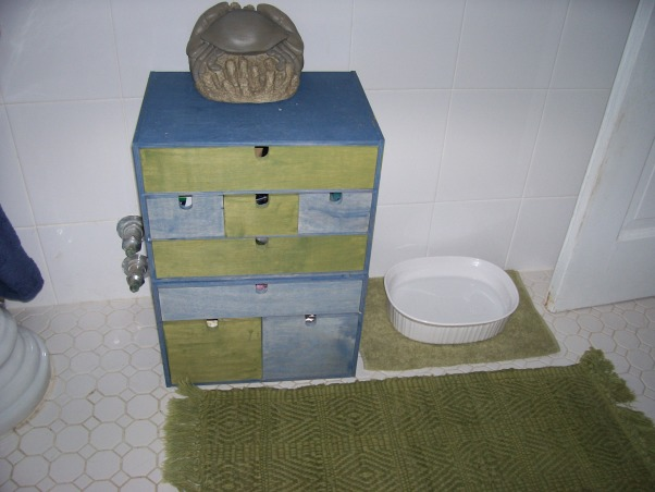 Small Seaside Bathroom, My only bathroom is tiny. Landlord doesn't want me painting it because he just renovated it before I moved in.  Tried to jazz it up with beach theme, but feel something is still lacking from making it pop. Really ugly and non-working fan is built into wall above toilet.  How can I mask it?, Needed more storage, so I painted these drawers from Ikea.  Dog water is next to them. Mirror (shown in other photo) is above. , Bathrooms Design