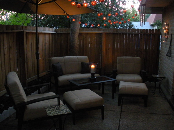 Our Back Patio Redo!, We live in a condo and have a small back patio/garden area.  For a long time, it was a very uninspiring space, full of weeds and old furniture.  We did not enjoy spending time out there!  I spotted a beautiful and affordable set of new patio furniture, and it inspired us to redo the whole space!  We just love spending time outside now, especially at night!, After - our new patio furniture!  This set was the inspiration for the whole space.  We love the clean lines and thick cushions.  We added an umbrella for shade because we live in Texas, and a nice hurricane vase with candle.  It's hard to see, but we replaced the old, rotten railroad ties with white stone border and replanted lots of very textural plants along the fence.  Looks MUCH better!  There is some landscape lighting in the border as well, and we just loved the string lights!  , Patios & Decks Design