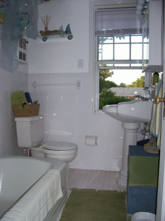 Small Seaside Bathroom, My only bathroom is tiny. Landlord doesn't want me painting it because he just renovated it before I moved in.  Tried to jazz it up with beach theme, but feel something is still lacking from making it pop. Really ugly and non-working fan is built into wall above toilet.  How can I mask it?, Bathrooms Design