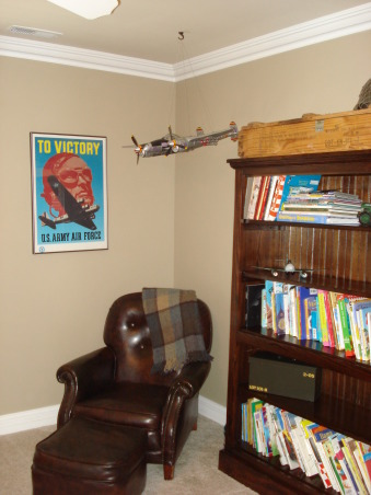 Vintage WWII Theme, I wanted a space for my twin boys that didn't use the bright primary colors and had a more muted pallet. The inspiration for this room was our families service in the Armed Forces.  The decor includes lots of toy planes and army antiques.  The large bookcase had no top and was in need of a lot of TLC--I got it for free when I purchased another item from an antique store.  I had it refinished and it turned out very nice.  I made the shadow boxes and got the WWII poster for about $8.00 on eBay.  The two beds were custom made in the same style as antique church bench. The pillows and bedspread were all clearance items.  The bed skirt and extra pillows were made from a striped fabric remnant that I found for $4.00 a yard.  , Boys' Rooms Design