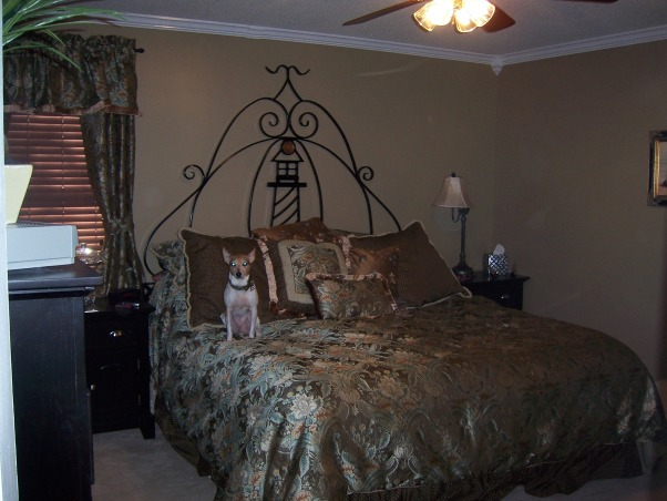 Lighthouse Bedroom, The bedroom is average size and accomodates a California King size bed with the custom iron headboard made by my husband., Walls painted a mushroom color, and crown molding installed.  Used those corner pieces you can buy at Lowes to avoid having to miter crown., Bedrooms Design