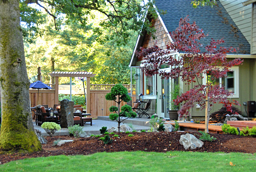 Northwest Outdoor Living...Oregon Style!, This past winter we completed a kitchen addition with doors that opened out into mud :) We've spent the last few weeks redoing our back yard.  The project included large boulders being brought in, new decks and bridges, dry stream bed, sprinkler systems, lighting, a fountain on the patio, concrete patio, new beds and plantings.  All in all we're really happy with the space. We already had a nice canopy of mature trees and in a few years, the new beds should fill in nicely.  We were inspired for this project by our love of the Portland Japanese Gardens. The foliage and simple lines seem to compliment nicely with northwest design. , Here you can see the privacy screen off the patio. Our swing set and basketball court are on the other side...the privacy screen makes a nice break between the two spaces. This photo was taken before the screen was stained. Gate to come soon...hopefully!                , Outdoor Spaces