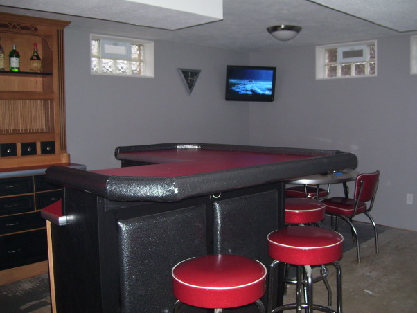 Retro 50s Bar, I built my basement bar-kitchen by myself on a very low budget.  I reused everything I could like 2 by 4s for the walls.  It is a work in progress. I do not want to finish the floor until the adjacent room is at least drywalled and mudded., I still have a lot of finish work to do but the new TV will keep me company while I do it.  Below the TV is a 50s laminate table with red chairs that match the bar stools.  It's a perfect place to play cards and watch a game.      , Basements Design