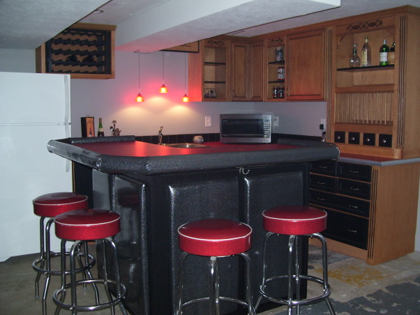 Retro 50s Bar, I built my basement bar-kitchen by myself on a very low budget.  I reused everything I could like 2 by 4s for the walls.  It is a work in progress. I do not want to finish the floor until the adjacent room is at least drywalled and mudded., This is just one more view of the bar area.  I don't call it a kitchen because it does not have a stove.  The lights above the sink look amber in the photos but are actually red.      , Basements Design