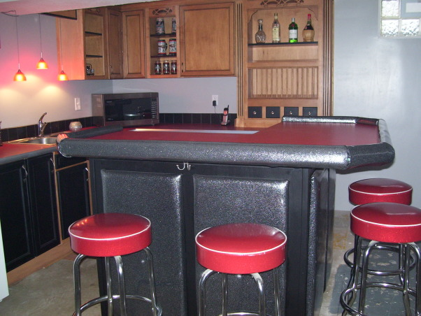 Retro 50s Bar, I built my basement bar-kitchen by myself on a very low budget.  I reused everything I could like 2 by 4s for the walls.  It is a work in progress. I do not want to finish the floor until the adjacent room is at least drywalled and mudded., This retro bar is padded with silver sparkle vinyl to match the 50s bar stools.  I wanted real wood cabinets instead of the laminate from the 50's but I tried to give them some personality with the black paint and chrome edging.  I actually used carpet edging for the chrome.       , Basements Design