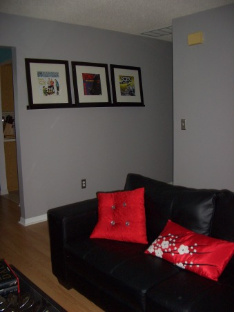 Black, Red and Gray Living Room, We already had a black and red color scheme for our living room from our previous place, so when we moved in here I was hard pressed to find a color besides the original mint green to paint the walls.  I ended up choosing gray, which everyone told me would make the space dark and gloomy, and am happy that I ignored the people that told me otherwise.  I still need to find a color for the wall with the window in it, as it still has the flower detailing and mint paint from the previous owner., I need to find a table of some kind to go under the punk albums.  I'm willing to take some suggestions. , Living Rooms Design