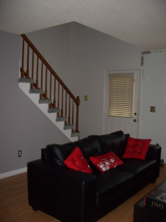 Black, Red and Gray Living Room, We already had a black and red color scheme for our living room from our previous place, so when we moved in here I was hard pressed to find a color besides the original mint green to paint the walls.  I ended up choosing gray, which everyone told me would make the space dark and gloomy, and am happy that I ignored the people that told me otherwise.  I still need to find a color for the wall with the window in it, as it still has the flower detailing and mint paint from the previous owner., I want to also change the front door and do something different with the stairs since they are such a part of this room.  Maybe paint the handrail white?  The carpet needs to go at the very least.   I'm getting a red hall table my mom made back in her interior design days to go along the stairs here.  , Living Rooms Design