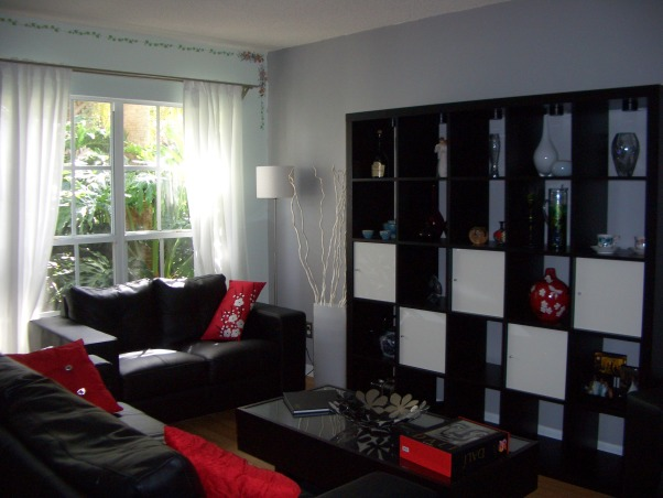 Black, Red and Gray Living Room, We already had a black and red color scheme for our living room from our previous place, so when we moved in here I was hard pressed to find a color besides the original mint green to paint the walls.  I ended up choosing gray, which everyone told me would make the space dark and gloomy, and am happy that I ignored the people that told me otherwise.  I still need to find a color for the wall with the window in it, as it still has the flower detailing and mint paint from the previous owner., The flowers over the window really need to go.  , Living Rooms Design