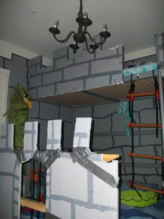 Dragon & Castle Room, Boys bedroom in the theme of a castle or dungeon complete with dragon!, I took the ikea loft bunk bed, added the rope ladder from ikea. For the castle pieces I took foam insulation board and covered it with plaster to make it hard prior to painting. Then I attached it to the bed with zip cords. Underneath the bed is another bed from Ikea with a piece duck tapped to it. Unfortunatly this piece was thinner and fell apart in transport so it's patched up for now. , Boys' Rooms Design