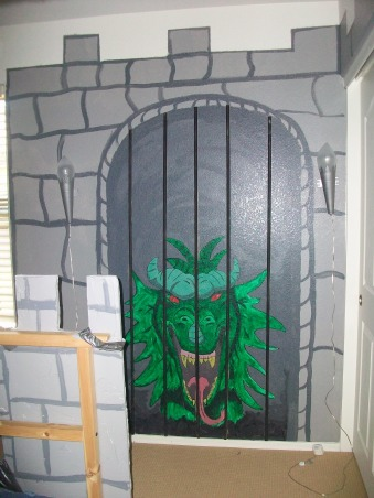 Dragon & Castle Room, Boys bedroom in the theme of a castle or dungeon complete with dragon!, I drew this dragon on the wall then painted it...it's about three feet high. On either side of the dungeon doorway you can see torch lamps (from Ikea as well. The bars were made from 1/2 round wood pieces painted black and glued on.  , Boys' Rooms Design