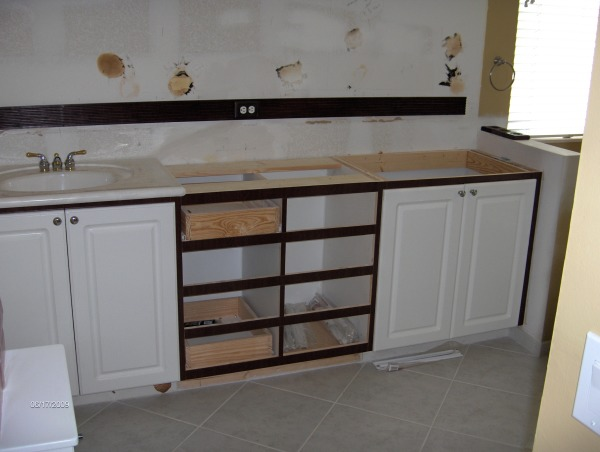 i did most of it myself, it was 10 years old and we were tired of all the white so i ripped into the cabinets and counter tops,i built a new cabinet in the center with eight drawers,and refaced the fronts,added a solid piece of granite and new sinks and faucets and ordered new doors and drawer fronts and had the painted dark brown, also removed the three huge mirror pieces and replaced it with a stained wood frame and a one piece mirror,my wife hated the shower enclosure so i took it out and replaced it with a frame less one and added new shower heads, also replaced the toilet with one that sits higher,the tile was in good shape so we didn't change it, and the cheep medicine cabinet i painted the silver frame and added a stained wood frame, the tub was in good shape so we kept it also,the whole thing was around $5000 dollars, refaced the front of the cabinets and added eight drawers in center section, Bathrooms Design