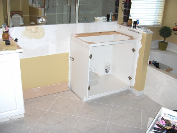 i did most of it myself, it was 10 years old and we were tired of all the white so i ripped into the cabinets and counter tops,i built a new cabinet in the center with eight drawers,and refaced the fronts,added a solid piece of granite and new sinks and faucets and ordered new doors and drawer fronts and had the painted dark brown, also removed the three huge mirror pieces and replaced it with a stained wood frame and a one piece mirror,my wife hated the shower enclosure so i took it out and replaced it with a frame less one and added new shower heads, also replaced the toilet with one that sits higher,the tile was in good shape so we didn't change it, and the cheep medicine cabinet i painted the silver frame and added a stained wood frame, the tub was in good shape so we kept it also,the whole thing was around $5000 dollars, ripped out center section and sink top began remodel, Bathrooms Design