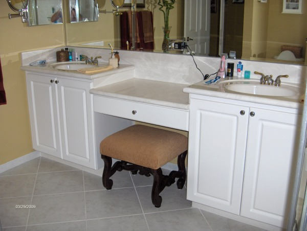 i did most of it myself, it was 10 years old and we were tired of all the white so i ripped into the cabinets and counter tops,i built a new cabinet in the center with eight drawers,and refaced the fronts,added a solid piece of granite and new sinks and faucets and ordered new doors and drawer fronts and had the painted dark brown, also removed the three huge mirror pieces and replaced it with a stained wood frame and a one piece mirror,my wife hated the shower enclosure so i took it out and replaced it with a frame less one and added new shower heads, also replaced the toilet with one that sits higher,the tile was in good shape so we didn't change it, and the cheep medicine cabinet i painted the silver frame and added a stained wood frame, the tub was in good shape so we kept it also,the whole thing was around $5000 dollars, old ugly plain white sinks and cabinet, Bathrooms Design