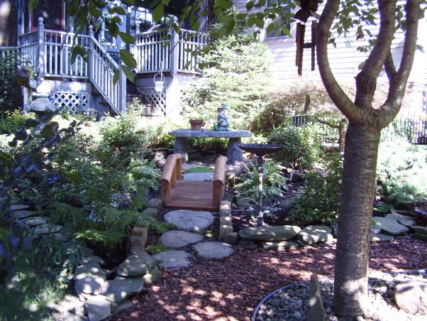 Backyard Escape, Our new backyard patio overlooks a small garden with pond and fountain., Small footbridge in shade garden.          , Gardens Design
