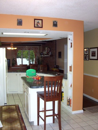 Tuscan 80s kitchen, This is our kitchen. When we moved in it was black and white and gray. Hence the white cabinets, gray floor tile and black/bluish-green marbley laminate counters. We went for more of a tuscan feel just to try to warm it up. My husband says a mini-remodel is at least 10 years off budget-wise but I like to plan ahead. :) I'm thinking of adding cabinets to the wall that currently houses our corner glassware cabinet and our little bistro set. We desperately need more storage - particularly pantry storage and small appliance storage. And then I'm pretty sure we need to take the island out completely. The area the island is in is just not big enough for an island. The passways are too tight for one person to get past another and when the dishwasher is open it practically scrapes across the island doors.... I will keep the bones of the kitchen though and probably the white cabinets... But I will want new flooring (many of the tiles are cracked), new conters, cabinets for the wall that currently doesn't have any..New lighting... Ideas are welcome..., Kitchens Design