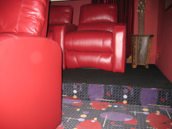 FAMILY  HOME  THEATER, From a room to view TV to a complete makeover media room.  Our 12' x 22' 16 ft ceiling room is now our home theatre.   Chianti red  double entry doors with awesome lion door handles (MGM LION). Enter into a theatre complete with Chianti red painted walls and ceiling. Leather reclining theatre seating  with base ambient lighting. Surround sound, wet bar turned into consession stand with commercial popcorn popper. Former coat closet turned into dvd storage with floor to ceiling shelves. We will be installing  soon a roll down screen on the wall above the tv and a projector to view movies. we plan to keep the TV for viewing HGTV. We achieved the dark space that you expect when going to the movies.  The colors we used were recommended by professionals. The red appears bright in our photos but in reality is subdued., Showing the back elevation.       , Home Theaters