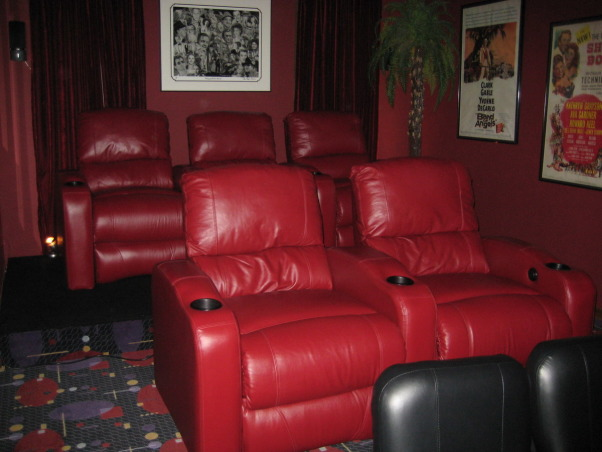 FAMILY  HOME  THEATER, From a room to view TV to a complete makeover media room.  Our 12' x 22' 16 ft ceiling room is now our home theatre.   Chianti red  double entry doors with awesome lion door handles (MGM LION). Enter into a theatre complete with Chianti red painted walls and ceiling. Leather reclining theatre seating  with base ambient lighting. Surround sound, wet bar turned into consession stand with commercial popcorn popper. Former coat closet turned into dvd storage with floor to ceiling shelves. We will be installing  soon a roll down screen on the wall above the tv and a projector to view movies. we plan to keep the TV for viewing HGTV. We achieved the dark space that you expect when going to the movies.  The colors we used were recommended by professionals. The red appears bright in our photos but in reality is subdued., Another view of our home theater.      , Home Theaters