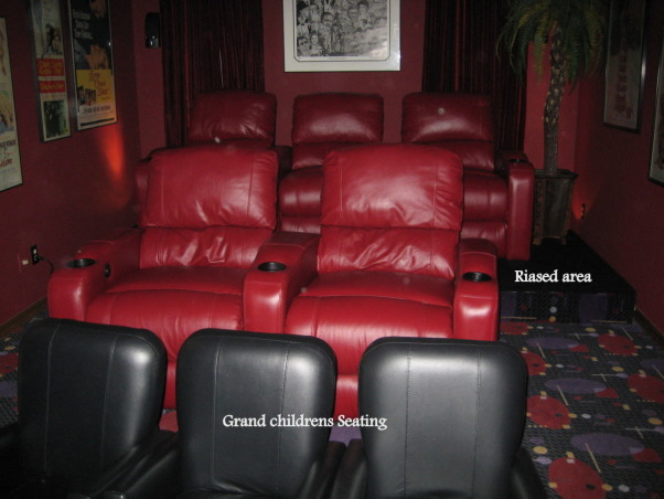 FAMILY  HOME  THEATER, From a room to view TV to a complete makeover media room.  Our 12' x 22' 16 ft ceiling room is now our home theatre.   Chianti red  double entry doors with awesome lion door handles (MGM LION). Enter into a theatre complete with Chianti red painted walls and ceiling. Leather reclining theatre seating  with base ambient lighting. Surround sound, wet bar turned into consession stand with commercial popcorn popper. Former coat closet turned into dvd storage with floor to ceiling shelves. We will be installing  soon a roll down screen on the wall above the tv and a projector to view movies. we plan to keep the TV for viewing HGTV. We achieved the dark space that you expect when going to the movies.  The colors we used were recommended by professionals. The red appears bright in our photos but in reality is subdued., Three rows of elevated seating gives everyone a good  seat      , Home Theaters