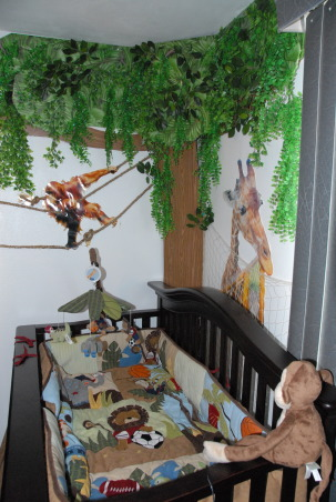 It's a Jungle in Here!, The goal in designing my son's room was that it be colorful, full of texture & three-dimensional.  Each scene is made up of at least three layers of media.  I tried to carry the jungle theme throughout the nursery by having branches continue through the verticle blinds & appear on the next wall. The trees were made out of foam board. Then we added contact paper, jungle themed paper & various layers of greenery. The animal photos were taken at various zoos & blown up to poster size (20 x 30). We cut them out & glued them to poster board then adhered them to the wall with liquid nails.  We used various shades of grasses & cattails over a green hill for the baby zebra scene.  The cheetah's rock was painted with Ralph Lauren River Rock paint to add a rough texture & completed the scene with tall grass.  Finally, the orangutan & giraffe have manilla rope & netting to give them an extra layer.  These will be removed once our baby boy is old enough to cause any havoc! ; )  It was a huge project that my niece, nephew & I worked on during my maternity leave. One pleasant surprise in the design was the movement in the greenery when the ceiling fan is on. The gentle rustling of the leaves & grass add a nice touch that really makes the room come alive. The nursery turned out just as I had hoped & I'm thrilled every time my newborn son curiously stares around at the jungle in his room! , Here you can see the layers of greenery, the netting on the giraffe photo & the manilla rope on the orangutan photo. The crib bedding continues the jungle theme.         , Nurseries Design
