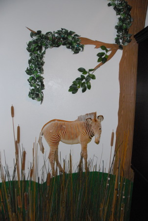 It's a Jungle in Here!, The goal in designing my son's room was that it be colorful, full of texture & three-dimensional.  Each scene is made up of at least three layers of media.  I tried to carry the jungle theme throughout the nursery by having branches continue through the verticle blinds & appear on the next wall. The trees were made out of foam board. Then we added contact paper, jungle themed paper & various layers of greenery. The animal photos were taken at various zoos & blown up to poster size (20 x 30). We cut them out & glued them to poster board then adhered them to the wall with liquid nails.  We used various shades of grasses & cattails over a green hill for the baby zebra scene.  The cheetah's rock was painted with Ralph Lauren River Rock paint to add a rough texture & completed the scene with tall grass.  Finally, the orangutan & giraffe have manilla rope & netting to give them an extra layer.  These will be removed once our baby boy is old enough to cause any havoc! ; )  It was a huge project that my niece, nephew & I worked on during my maternity leave. One pleasant surprise in the design was the movement in the greenery when the ceiling fan is on. The gentle rustling of the leaves & grass add a nice touch that really makes the room come alive. The nursery turned out just as I had hoped & I'm thrilled every time my newborn son curiously stares around at the jungle in his room! , The zebra foal print is the first layer followed by the green hill made of foam board. The top layer is a variety of grasses & cattails. The leaves & grasses move gently when the fan is on!         , Nurseries Design