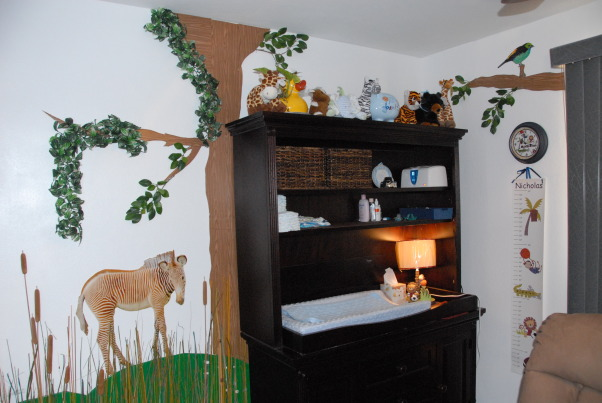 It's a Jungle in Here!, The goal in designing my son's room was that it be colorful, full of texture & three-dimensional.  Each scene is made up of at least three layers of media.  I tried to carry the jungle theme throughout the nursery by having branches continue through the verticle blinds & appear on the next wall. The trees were made out of foam board. Then we added contact paper, jungle themed paper & various layers of greenery. The animal photos were taken at various zoos & blown up to poster size (20 x 30). We cut them out & glued them to poster board then adhered them to the wall with liquid nails.  We used various shades of grasses & cattails over a green hill for the baby zebra scene.  The cheetah's rock was painted with Ralph Lauren River Rock paint to add a rough texture & completed the scene with tall grass.  Finally, the orangutan & giraffe have manilla rope & netting to give them an extra layer.  These will be removed once our baby boy is old enough to cause any havoc! ; )  It was a huge project that my niece, nephew & I worked on during my maternity leave. One pleasant surprise in the design was the movement in the greenery when the ceiling fan is on. The gentle rustling of the leaves & grass add a nice touch that really makes the room come alive. The nursery turned out just as I had hoped & I'm thrilled every time my newborn son curiously stares around at the jungle in his room! , This is the changing table area surrounded by animals.        , Nurseries Design