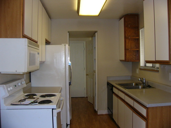 "Lackluster Laminate , Dark, narrow, galley kitchen with laminate from floor to ceiling., 1980's era kitchen with laminate from floor to ceiling, very dark and closed off from the rest of the house, depressing to stare at a dirty non-functional microwave while cooking. I painted the walls a light ""Sandstone Cove"" to brighten it up but it is still very dark.  Can anyone help me and tell me how to make my galley kitchen feel larger when I can't afford to simply blow off the back of the house as I would like to?       , Kitchens Design"