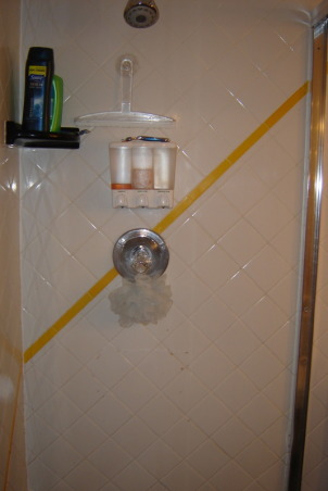 1970's color mess , The space from bathroom past. The walls are graced with white tile which wouldn't be too bad if the diagonal stripes of bright yellow, red and black didn't smack you in the face. The cabinet is white formica with a cherry red counter top and black sink. Above the cabinet is a mirror and lighting that makes you feel as though you should be backstage applying theater makeup. The shower is bizarre. You can enter it from two areas, a set of sliders or a shower door from the master bathroom. It has a black tile floor which I feel always looks grungy. Oh, lets not forget the faux black marble floor everywhere else. Yuk! Please Help!!         , Shower wall with bright yellow accent stripe and black soap holder., Bathrooms Design