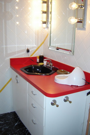 1970's color mess , The space from bathroom past. The walls are graced with white tile which wouldn't be too bad if the diagonal stripes of bright yellow, red and black didn't smack you in the face. The cabinet is white formica with a cherry red counter top and black sink. Above the cabinet is a mirror and lighting that makes you feel as though you should be backstage applying theater makeup. The shower is bizarre. You can enter it from two areas, a set of sliders or a shower door from the master bathroom. It has a black tile floor which I feel always looks grungy. Oh, lets not forget the faux black marble floor everywhere else. Yuk! Please Help!!         , Cherry red formica counter top with black six sided sink. Two tone faucet., Bathrooms Design