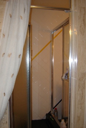 1970's color mess , The space from bathroom past. The walls are graced with white tile which wouldn't be too bad if the diagonal stripes of bright yellow, red and black didn't smack you in the face. The cabinet is white formica with a cherry red counter top and black sink. Above the cabinet is a mirror and lighting that makes you feel as though you should be backstage applying theater makeup. The shower is bizarre. You can enter it from two areas, a set of sliders or a shower door from the master bathroom. It has a black tile floor which I feel always looks grungy. Oh, lets not forget the faux black marble floor everywhere else. Yuk! Please Help!!         , Bathrooms Design
