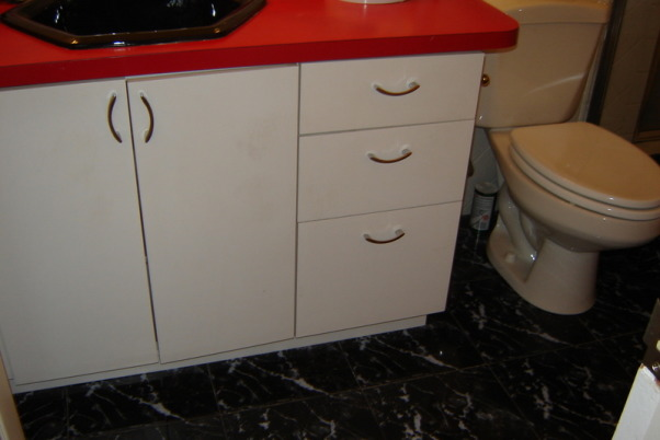1970's color mess , The space from bathroom past. The walls are graced with white tile which wouldn't be too bad if the diagonal stripes of bright yellow, red and black didn't smack you in the face. The cabinet is white formica with a cherry red counter top and black sink. Above the cabinet is a mirror and lighting that makes you feel as though you should be backstage applying theater makeup. The shower is bizarre. You can enter it from two areas, a set of sliders or a shower door from the master bathroom. It has a black tile floor which I feel always looks grungy. Oh, lets not forget the faux black marble floor everywhere else. Yuk! Please Help!!         , White formica cabinet on top of faux black marble floor., Bathrooms Design
