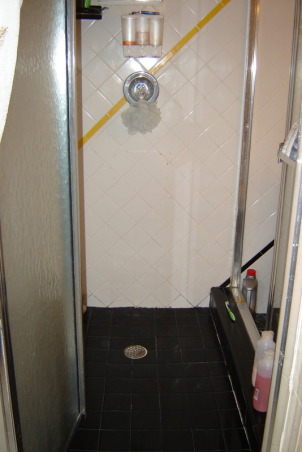 1970's color mess , The space from bathroom past. The walls are graced with white tile which wouldn't be too bad if the diagonal stripes of bright yellow, red and black didn't smack you in the face. The cabinet is white formica with a cherry red counter top and black sink. Above the cabinet is a mirror and lighting that makes you feel as though you should be backstage applying theater makeup. The shower is bizarre. You can enter it from two areas, a set of sliders or a shower door from the master bathroom. It has a black tile floor which I feel always looks grungy. Oh, lets not forget the faux black marble floor everywhere else. Yuk! Please Help!!         , Ugly, dingy black shower floor , Bathrooms Design