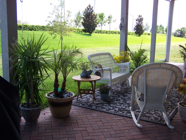 Cottage Lanai , We have a 60' x 10' brick lanai behind our house.  We also have a huge backyard with nothing in it because we don't know what to do with the space.  We have a lot of furniture and plants crammed into this brick space but nothing in the yard.  We wanted to build a pool but can't afford it so now we'd like to somehow utilize the space but don't know how., This is another angle of the lanai.  Again, you can see that there is a lot of wasted space in the yard. , Patios & Decks Design