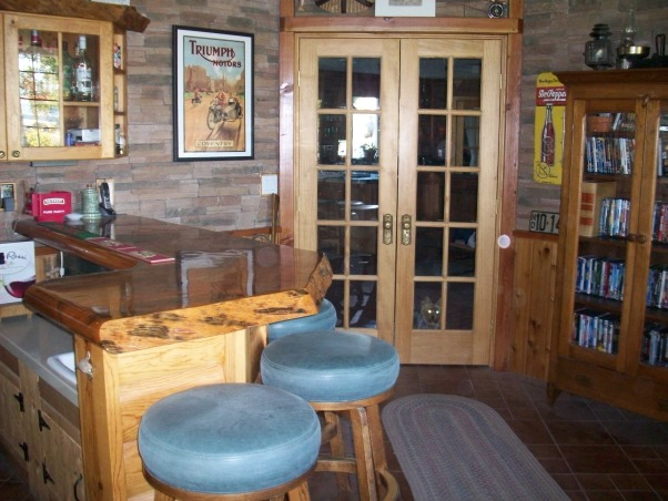 Rustic Man Cave/Bar, This entire room was done by my dad for himself. Starting with the pine French doors entering the man cave with huge pine logs. He placed brown tiles on the floor rotating different sized tiles. The chair rail is pine with slated stone that meets at the ceiling with more pine beams. He painted the ceiling in a forest green. The bar top is a solid pine tree truck that is coated in lacquer with under rope lighting. He enclosed the refrigerator behind the same door as the French doors, but took out the bottom glass panels for air. The bar counter top is a solid white corian with a small bar sink. Storage underneath and above bar. About the refrigerator is a small spot for all electronics for the TV which is covered in corks. The bar table is permanent in the ground and has a slate top. He added a small couch with a pull out twin bed., Other Spaces Design