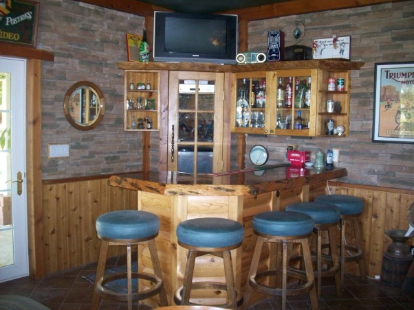 Rustic Man Cave/Bar, This entire room was done by my dad for himself. Starting with the pine French doors entering the man cave with huge pine logs. He placed brown tiles on the floor rotating different sized tiles. The chair rail is pine with slated stone that meets at the ceiling with more pine beams. He painted the ceiling in a forest green. The bar top is a solid pine tree truck that is coated in lacquer with under rope lighting. He enclosed the refrigerator behind the same door as the French doors, but took out the bottom glass panels for air. The bar counter top is a solid white corian with a small bar sink. Storage underneath and above bar. About the refrigerator is a small spot for all electronics for the TV which is covered in corks. The bar table is permanent in the ground and has a slate top. He added a small couch with a pull out twin bed., This is the bar area., Other Spaces Design