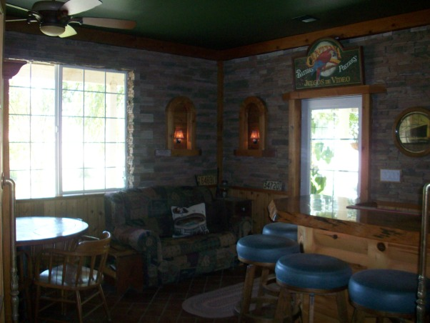 Rustic Man Cave/Bar, This entire room was done by my dad for himself. Starting with the pine French doors entering the man cave with huge pine logs. He placed brown tiles on the floor rotating different sized tiles. The chair rail is pine with slated stone that meets at the ceiling with more pine beams. He painted the ceiling in a forest green. The bar top is a solid pine tree truck that is coated in lacquer with under rope lighting. He enclosed the refrigerator behind the same door as the French doors, but took out the bottom glass panels for air. The bar counter top is a solid white corian with a small bar sink. Storage underneath and above bar. About the refrigerator is a small spot for all electronics for the TV which is covered in corks. The bar table is permanent in the ground and has a slate top. He added a small couch with a pull out twin bed., The view when you enter., Other Spaces Design