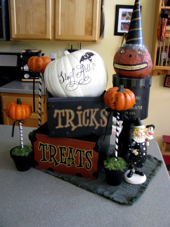 "Halloween by Michelle, Halloween, for me, is about magic and whimsy.  I like decorating with a ""Yester-year"" style, using little witches and black cats,  paper mache pumpkin heads and crate paper ruffles.  My haunt, inside and out, is ""little kid friendly"" and I won't put anything up that will scare them.     , The three pumpkin's in flower pots were made by me -copying and modifying a great idea from a Halloween magazine- as was the white pumpkin.  I painted the pumpkin antique white and drew all that on with a sharpie.            , Holidays Design"