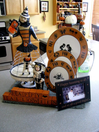 "Halloween by Michelle, Halloween, for me, is about magic and whimsy.  I like decorating with a ""Yester-year"" style, using little witches and black cats,  paper mache pumpkin heads and crate paper ruffles.  My haunt, inside and out, is ""little kid friendly"" and I won't put anything up that will scare them.     , Just things I've collected.  That wire dress clown is one of my favorites.  In the black frame is a photo of me and my husband dressed up for Halloween -I'm a severed head, he's a mad scientist.            , Holidays Design"