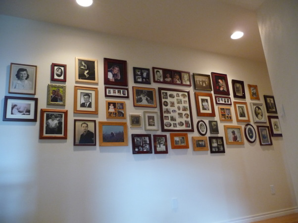 Family Photo Gallery, My entry hall was bland and boring until I hung a collection of family photos., I decided not to match frames, but instead to make the gallery appear as it was collected over time.  To plan the layout, I marked a space on the floor that was the same dimensions, laid out the frames and when I was satisfied, I started hanging from the middle out.  I removed the stands from the frames so they would lay flat on the wall. , Living Rooms Design