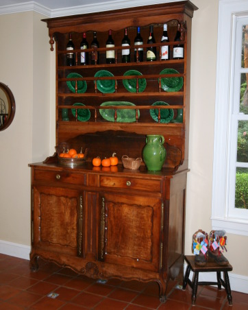 Back Hallway/Mudroom, I don't know what to call this area other than a back hallway or mud room.  It is actually a side entrance, but 95% of our visitors come in this door because it is closest to the driveway., A 19th C French Cherry Deux Corps holding our majolica plates and bottlees of wine on the top shelf.  My LL Bean boots sit on a small stool displaying all my tags from many of the antique shows I visited while living in the UK.  It was so much fun as the dealers and the buyers all enter the grounds at the same time.  Many times the best buys are purchased within the trade before the buyers enter the show.  In England, I had so much fun attending these shows as it was so exciting to find a great buy and there were so many treasures.   , Other Spaces Design