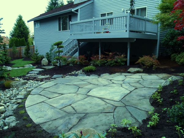 Japanese Zen Backyard, Just completed Zen backyard using plants that are native to the Pacific Northwest.  This is wonderful design for small backyard spaces., From the same angle, the patio was placed in the wider part of the triangle.  Underneath the front of the deck are 7 Nandina that will grow taller and screen any wheelbarrows and such from view.  On both sides of the stairs I needed something that would not bush out and grow into the deck railing so on the right side there is a Poodle Pine and on the left side is a dwarf blue Cupressus Arizonica with black grass planted in front of it for what I hope to be a dramatic effect.  Surrounding the stepping stones we were originally going to use a pea gravel but with three dogs.....didn't want that spread all around the yard so we used two different colors of ajuga.  When they fill in around the stepping stones it should create another river effect.  The entire yard is covered with black mulch.    , Yards Design
