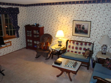 english cottage look, living room/music studio. This is where I teach violin.  The Ethan Allen love seats were given to me by my parents as hand me downs, and I never got around to replacing them. The wall paper was my attempt at coordinating with the rather plain looking love seats, and creating kind of an English cottage look.  I might be ready for a complete makeover.  The pink carpet is stained and needs to go., the seating actually works pretty well for waiting parents and home recitals, Living Rooms Design