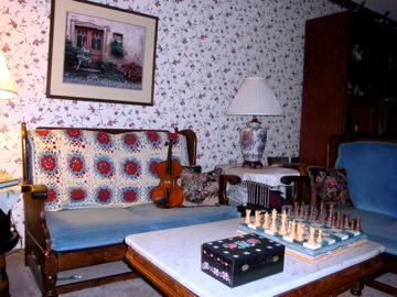 english cottage look, living room/music studio. This is where I teach violin.  The Ethan Allen love seats were given to me by my parents as hand me downs, and I never got around to replacing them. The wall paper was my attempt at coordinating with the rather plain looking love seats, and creating kind of an English cottage look.  I might be ready for a complete makeover.  The pink carpet is stained and needs to go., I may be ready for a complete makeover.  This room started with hand me down love seats from my parents and that was 20 years ago.  Wall paper and pink carpet were popular in the early 80's. , Living Rooms Design