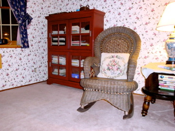 english cottage look, living room/music studio. This is where I teach violin.  The Ethan Allen love seats were given to me by my parents as hand me downs, and I never got around to replacing them. The wall paper was my attempt at coordinating with the rather plain looking love seats, and creating kind of an English cottage look.  I might be ready for a complete makeover.  The pink carpet is stained and needs to go., I like the wicker rocking chair and the book case is convenient for storing my sheetmusic, Living Rooms Design