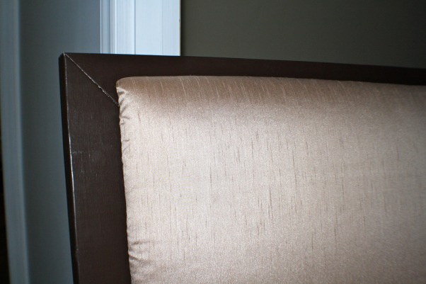"Homemade Headboard, This is the bedroom at my last apartment. The comforter is from Bed, Bath and Beyond and pretty much everything else is from Target. I made the headboard myself with 2x6 wood, foam batting and material from a clearance drapery panel at Marshall's. The wall color is Valspar's ""Polished Silver"", Close up shot of the headboard. You can see my corners don't quite line up. This was because I screwed the pieces together by myself and I really needed someone else to hold them in place while I attached them. I plan to take it apart and line it up correctly at some point. You can't tell from far away, but obviously its noticeable up close.   , Bedrooms Design"