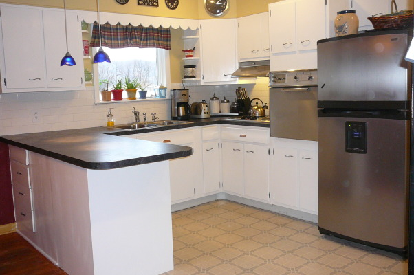 "1959 Kitchen Gets Makeover with White Painted Cabinets!, We did a mini makeover our 1959 kitchen with old worn cabinets and the classic white formica with gold flecks. It cost us less than $3000 to do this and a little more than half of that cost was for the new countertops, rest was for new sink, cooktop, paint, primer and various supplies.   How we did it: We sanded all cabinet bases, doors and drawers and primered with Zinnser BIN primer (THE BEST!) and 2-3 coats of ""piano key"" white Valspar semi-gloss brushed on with a good 2.5"" brush (don't try spraying it was a disaster!). New GE stainless cooktop and ACE stainless sink, new subway tile backsplash. All hardware stripped down to steel base, and clear-coated with Rustoleum. We will be putting in a new floor either continuing the oak hardwood into the kitchen or putting in slate. The Formica is black slate in the ""honed"" finish. It looks and feels like slate and has slight white grain running through it. Nearly indestructible and 1/10 the price of granite!! , Kitchen finished (except floor)          , Kitchens Design"