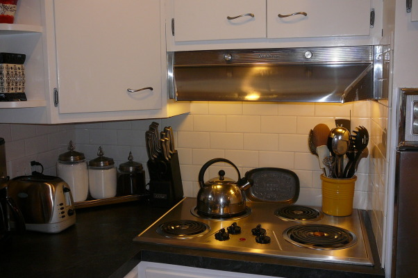 "1959 Kitchen Gets Makeover with White Painted Cabinets!, We did a mini makeover our 1959 kitchen with old worn cabinets and the classic white formica with gold flecks. It cost us less than $3000 to do this and a little more than half of that cost was for the new countertops, rest was for new sink, cooktop, paint, primer and various supplies.   How we did it: We sanded all cabinet bases, doors and drawers and primered with Zinnser BIN primer (THE BEST!) and 2-3 coats of ""piano key"" white Valspar semi-gloss brushed on with a good 2.5"" brush (don't try spraying it was a disaster!). New GE stainless cooktop and ACE stainless sink, new subway tile backsplash. All hardware stripped down to steel base, and clear-coated with Rustoleum. We will be putting in a new floor either continuing the oak hardwood into the kitchen or putting in slate. The Formica is black slate in the ""honed"" finish. It looks and feels like slate and has slight white grain running through it. Nearly indestructible and 1/10 the price of granite!! , Backsplash with new cooktop (original hood though)          , Kitchens Design"