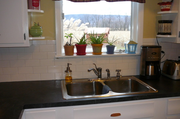 "1959 Kitchen Gets Makeover with White Painted Cabinets!, We did a mini makeover our 1959 kitchen with old worn cabinets and the classic white formica with gold flecks. It cost us less than $3000 to do this and a little more than half of that cost was for the new countertops, rest was for new sink, cooktop, paint, primer and various supplies.   How we did it: We sanded all cabinet bases, doors and drawers and primered with Zinnser BIN primer (THE BEST!) and 2-3 coats of ""piano key"" white Valspar semi-gloss brushed on with a good 2.5"" brush (don't try spraying it was a disaster!). New GE stainless cooktop and ACE stainless sink, new subway tile backsplash. All hardware stripped down to steel base, and clear-coated with Rustoleum. We will be putting in a new floor either continuing the oak hardwood into the kitchen or putting in slate. The Formica is black slate in the ""honed"" finish. It looks and feels like slate and has slight white grain running through it. Nearly indestructible and 1/10 the price of granite!! , backsplash sink and counters finished... subway tile is classic, easy and at .24 a piece (lowe's) SUPER cheap. Cost less than $50!          , Kitchens Design"