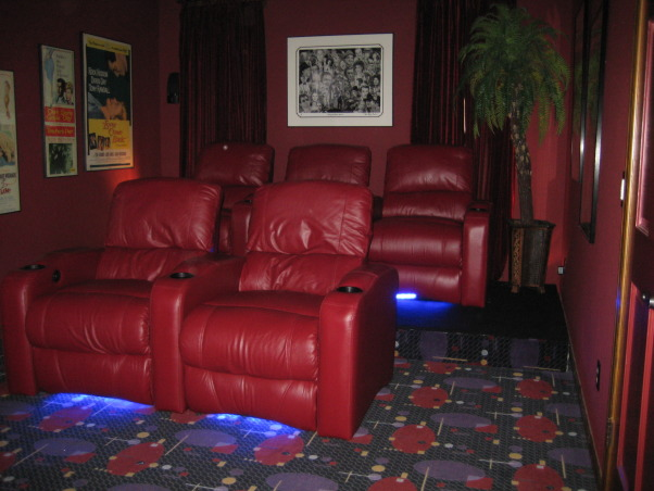FAMILY  HOME  THEATER, From a room to view TV to a complete makeover media room.  Our 12' x 22' 16 ft ceiling room is now our home theatre.   Chianti red  double entry doors with awesome lion door handles (MGM LION). Enter into a theatre complete with Chianti red painted walls and ceiling. Leather reclining theatre seating  with base ambient lighting. Surround sound, wet bar turned into consession stand with commercial popcorn popper. Former coat closet turned into dvd storage with floor to ceiling shelves. We will be installing  soon a roll down screen on the wall above the tv and a projector to view movies. we plan to keep the TV for viewing HGTV. We achieved the dark space that you expect when going to the movies.  The colors we used were recommended by professionals. The red appears bright in our photos but in reality is subdued., Home Theaters